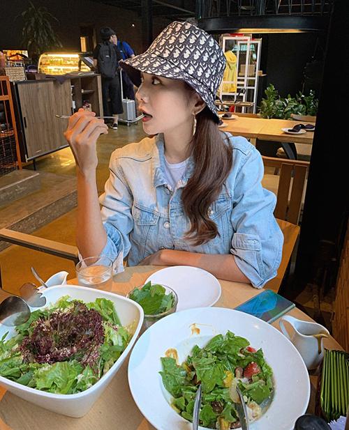 Đội mũ bucket ngồi ăn, Thanh Hằng trông trẻ trung như teen girl.