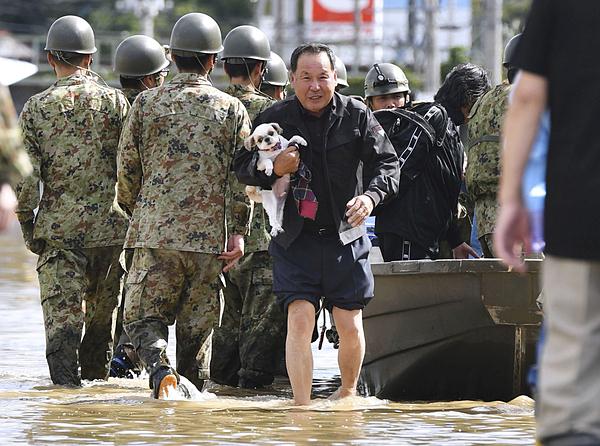 Một người đàn ông giải cứu chó cưng của mình khỏi khu vực ngập nước tại thành phố Motomiya, tỉnh Fukushima, Nhật Bản. Ảnh: Reuters.