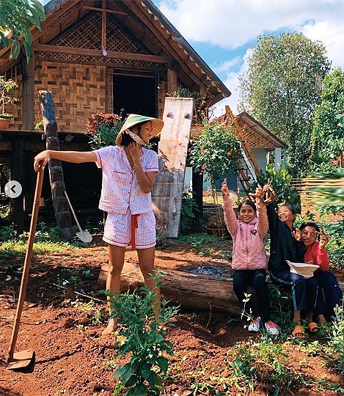 HHen Niê mặc đồ ngủ giản dị, ra vườn cuốc đất, chơi cùng các em nhỏ trong làng.