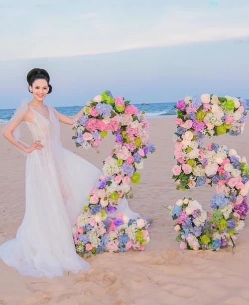 Sang Lê tạo dáng bên số 25, được kết bằng hoa tươi.