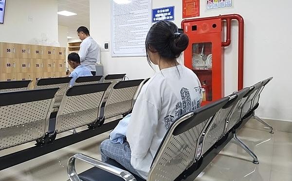Phạm Thị Hoa ngồi chờ vào phòng trị xạ.