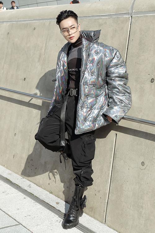 Đổ bộ tại con đường streetstyle nổi tiếng tại Hàn Quốc, Ti Ti tinh tế chọn cho mình set đồ rất bắt mắt khi phối áo thun cổ lọ đậm chất sporty cùng quần jogger túi hộp tong xuyệt tông đen cool ngầu. Tất nhiên, điểm nhấn không thể bỏ qua chính là chiếc nịt bằng chốt khóa bản to độc đáo. Và để tăng thêm độ chất lừ, Ti Ti đã khoác ngoài một chiếc áo phao với chất liệu metallic ánh bạc, bắt sáng cùng những chiếc nút vải đồng điệu trải khắp item này.