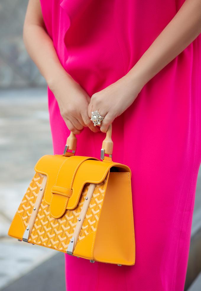 <p> Bộ váy với phom rộng, có điểm nhấn ở hoạ tiết hoa to bản được Diễm My kết hợp với túi Goyard màu vàng cam bắt mắt.</p>