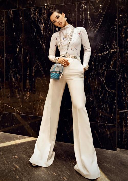 Tham dự sự kiện thời trang mới đây, Khánh Linh diện phong cách cá tính với cả cây đồ trắng đi kèm phụ kiện Chanel. Điểm nhấn trên trang phục của cô là chiếc túi xách đeo chéo, mang tông màu xanh dương khác biệt.