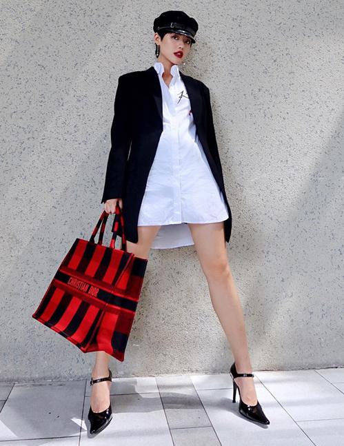 Khánh Linh bổ sung thêm một chiếc túi hiệu vào gia tài đồ sộ. Chiếc Dior Tote màu đỏ đen làm điểm nhấn hoàn hảo cho set đồ màu đen trắng của cô nàng.