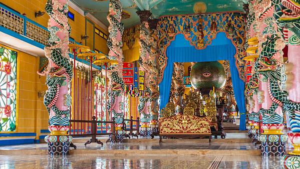 Đền Cao Đài nằm ở làng Long Thần, phía Tây Bắc TP HCM. Đền được xây dựng vào năm 1955. Bên trong ngôi đền mái vòm đầy màu sắc, bạn sẽ thấy mọi vị thần từ Chúa Jesus đến Đức Phật cũng như những cây cột được chạm khắc công phu. Ảnh: AFP.