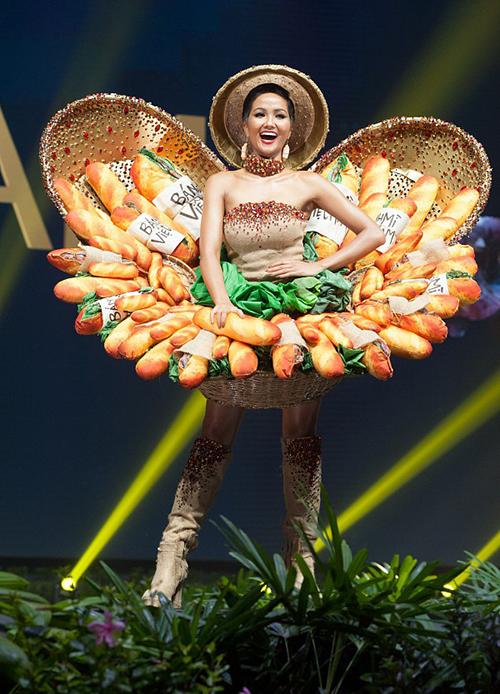 HHen Niê trình diễn Bánh mì trong phần thi trang phục truyền thống thuộc khuôn khổ Miss Universe 2018 tại Thái Lan. Người đẹp diện thiết kế lấy cảm hứng từ bánh mì - món ăn đường phố nổi tiếng kết hợp váy quây và nón lá. Người trong êkíp của HHen Niê tiết lộ với Ngoisao.net rằng cô đã gặp sự cố hỏng mắc gài ngay trước đêm thi khiến phần mô hình bánh mì không được định hình vững chắc như ban đầu
