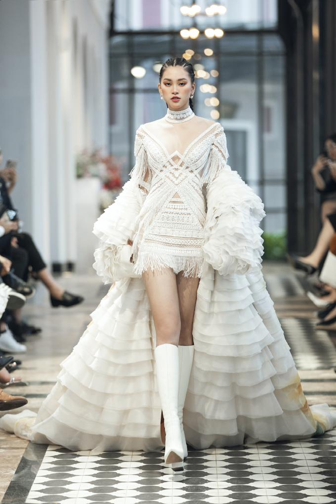 <p> Hoa hậu Tiểu Vy đảm nhận vai trò kết màn cho show diễn đặc biệt của nhà thiết kế Lê Thanh Hòa. Người đẹp diện bộ trang phục trắng cá tính, kết hợp cùng kiểu tóc độc đáo, tự tin sải bước trên sàn diễn.Điểm nhấn của thiết kế này nằm ở chiếc áo choàng lớn in khung cảnh thiên nhiên Tây Bắc.</p>