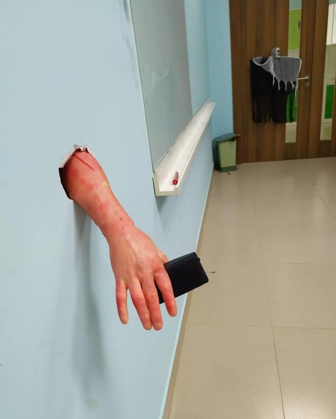 """<p> Nguyễn Hà My, học sinh lớp 12A1 trường THPT FPT, chia sẻ: """"Ý tưởng trang trí lớp Halloween của lớp mình bắt đầu từ việc có một lỗ hổng trên tường bị vỡ gần bảng , tụi mình tận dụng chỗ hở đó để làm hình nộm bằng tay giả giống như tay chui ra từ tường luôn"""".</p>"""