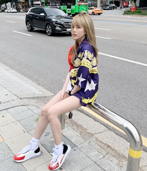 Áo sơ mi Versace diện theo cách giấu quần giúp Thiều Bảo Trâm khoe da trắng, chân dài.
