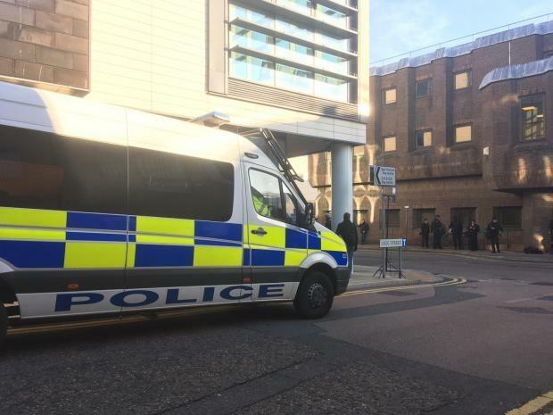 Cảnh sát ở bên ngoài tòa án nơi diễn ra phiên tòa sơ thẩm.
