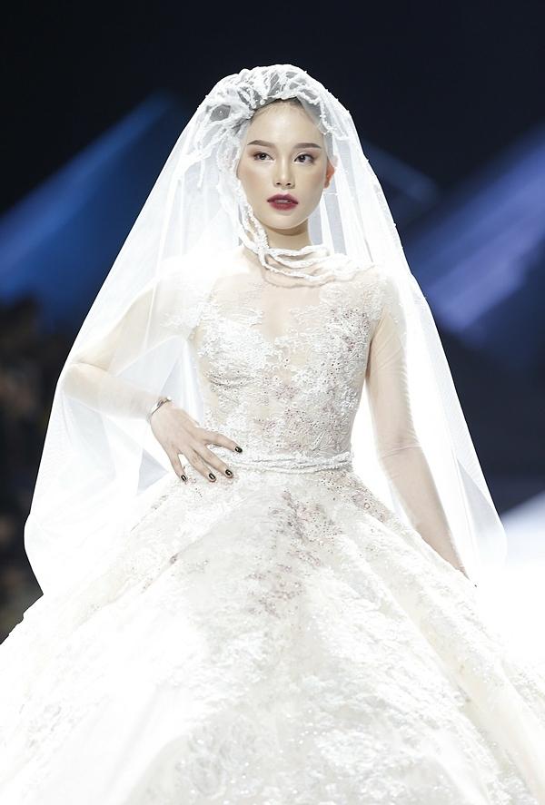 Trở thành vedette của đêm diễn, Linh Rin diện váy xòe bồng bềnh với phần vải xuyên thấu bên trên, giúp người đẹp khoe làn da trắng mịn màng. Phần khăn voan trùm đầu được thiết kế độc đáo thu hút ánh nhìn người xem.