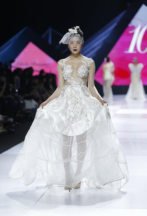 Với ngôn ngữ của nếp vải, nhà thiết kế kết hợp những mảng trong đục huyền ảo của gam màu trắng cùng họa tiết sắp đặt ngẫu hứng từ ren như muốn thể hiện cung bậc cảm xúc mạnh mẽ, đầy cám dỗ của những ai từng trải qua tình yêu.