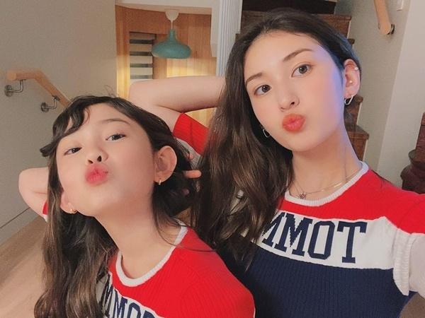 Jeon Somi và em gái mặc đồ đôi, tạo dáng đồng điệu.
