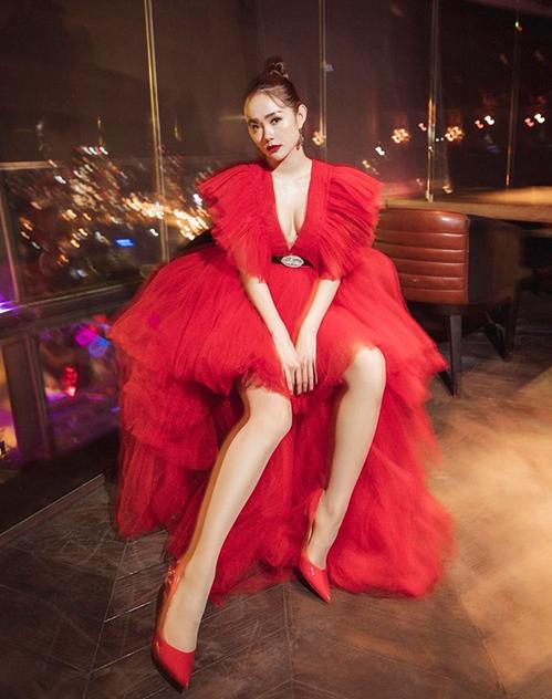 Trong buổi diễn mới đây, Minh Hằng chọn thiết kế lộng lẫy, màu đỏ rực nổi bật. Bộ trang phục có kiểu dáng xẻ cổ sâu tôn vòng một, chất liệu chiffon xếp lớp bồng bềnh tựa công chúa.