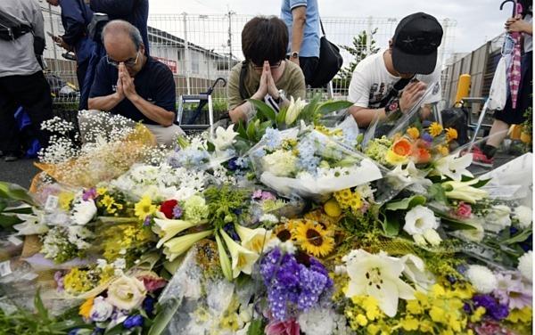 Người dân đặt hoa cầu nguyện cho nạn nhân vụ hỏa hoạn. Ảnh: Kyodo.