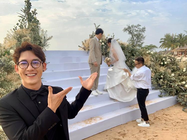 Không kịp thời gian chụp hình cùng Đông Nhi - Ông Cao Thắng trước giờ làm lễ, Song Luân đành chọn cách... chụp ké khi cả hai đang chuẩn bị.
