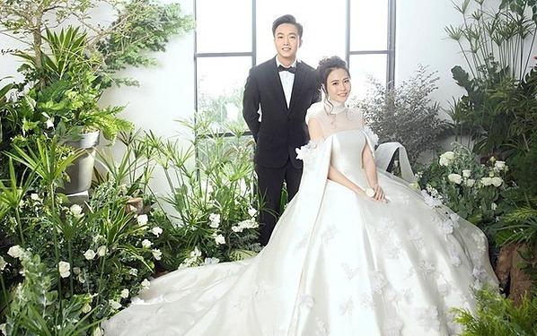 Váy cưới được đặt riêngTrong lễ cưới, Đàm Thu Trang thay ba bộ váy. Trong đó, bộ váy chínhdo NTK Trần Hùng chuẩn bị trong một tháng cho Đàm cô nhậnnhiều lời khen ngợi.Chất liệu của chiếc váy là mikado 100% lụa. Đây là chất liệu hàng đầu mà các nhà mốt danh tiếng thường sử dụng trong thiết kế đồ cưới. Theo chia sẻ từ Trần Hùng, giá thành loại vải này khá đắt, rất ít nhà mốt ở Việt Nam sử dụng nên việc tìm kiếm rất khó khăn.Thiết kế này tiêu tốn hơn 30m vải mikado. Phần lót của váy, tôi sử dụng taffeta 100% lụa. Thân trên của thiết kế làm từ lụa organza cùng tulle cao cấp của Italy. Những bông hoa trên váy cũng được làm hoàn toàn thủ công từ organza kết hợp cùng đá swarovski.