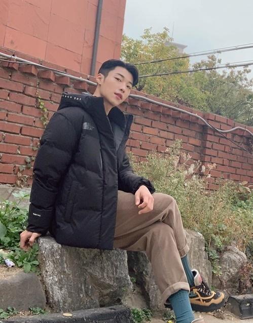 Woo Do Hwan ngồi vắt chân, hất mặt đầy thần thái.