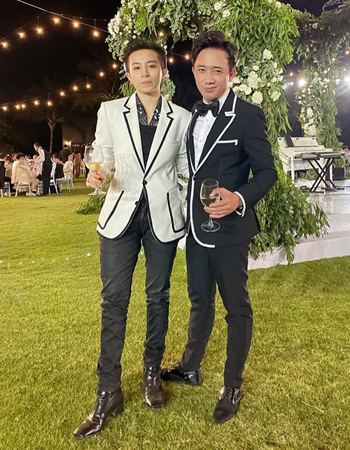 Gil Lê và Trấn Thành mặc tông xuyệt tông, một người diện vest trắng viền đen, một người vest đen viền trắng.
