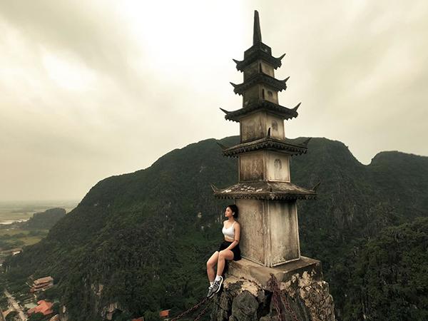 Miu Lê ngồi vắt vẻo chụp hình ở Hang Múa, Ninh Bình.