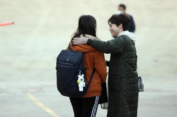 <p> Cha mẹ đi cùng con đến trường thi. Trong ảnh, một người mẹ chúc con gái làm bài kiểm tra tốt trên đường dẫn đến Trường trung học Namsan ở Daegu.</p>