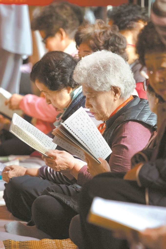 <p> Người bà ngồi đọc kinh cầu nguyện.</p>