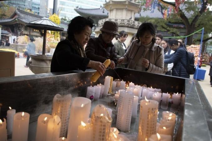 <p> Bên trong ngôi đền, du khách thắp nến để mong con em mình vượt qua kỳ thi kiểm tra năng lực.</p>