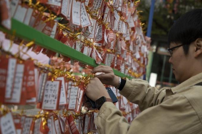 <p> Một du khách treo tấm bùa chú (được gọi là Yut) viết lời cầu nguyện - nơi hàng nghìn người viết bùa chú may mắn cho người thân.</p>
