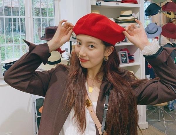 Suzy nhí nhảnh đội thử mũ chiếc mũ beret đỏ.