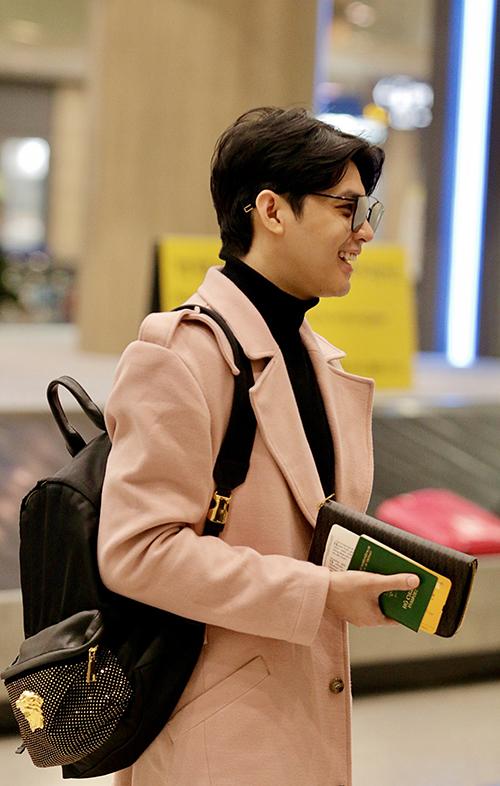Anh gây ấn tượng với phong cách thời trang chuẩn nam thần xứ Hàn khi diện nguyên set đồ đen với điểm nhấn là áo măng tô màu hồng dáng dài.