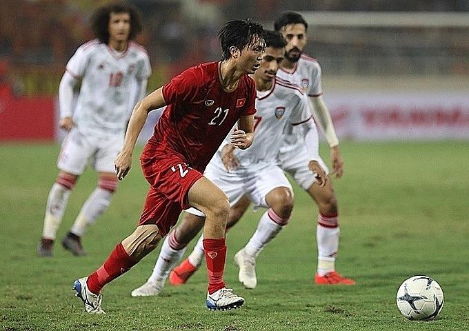 Tuấn Anh trong vòng vây của các cầu thủ UAE.