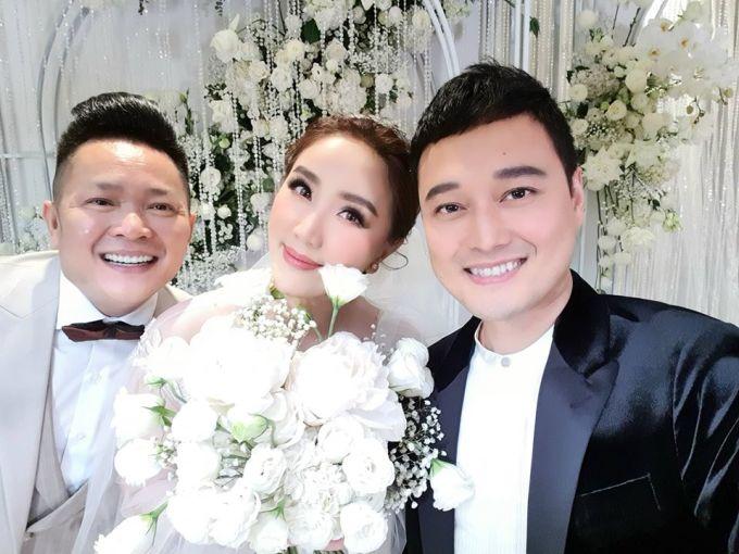 <p> Quang Vinh chụp ảnh cùng cô dâu - chú rể.</p>