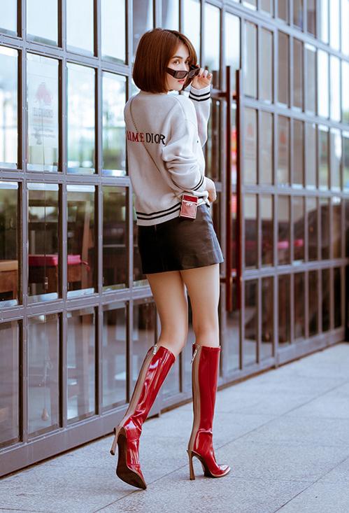 Áo len Dior được Ngọc Trinh kết hợp cùng chân váy da siêu ngắn khoe chân dài.