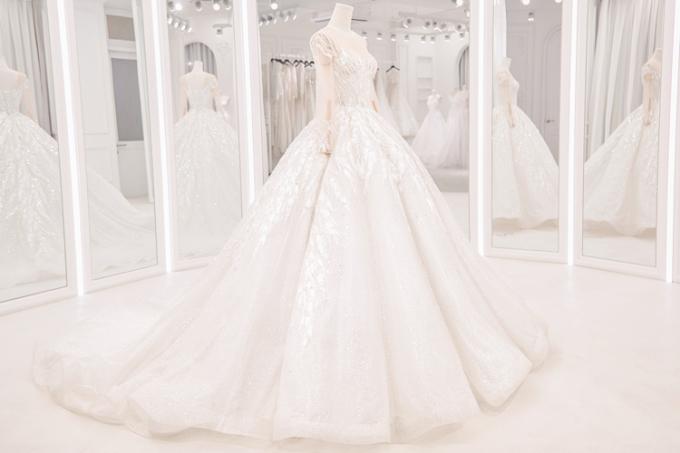 tùng váy bồng xoè, đuôi dài khoảng 2 mét, kiểu dáng corset siết eo, tay áo dài cổ điển cũng là điểm nhấn đắt giá cho bộ trang phục cưới lộng lẫy lần này.