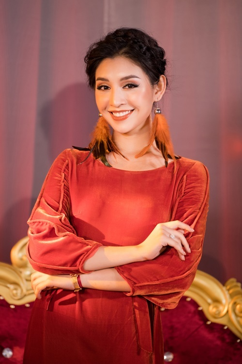 Lê Thanh Tú diện áo dài màu cam đất với điểm nhấn là phần bèo nhún ở hai bên cánh tay.