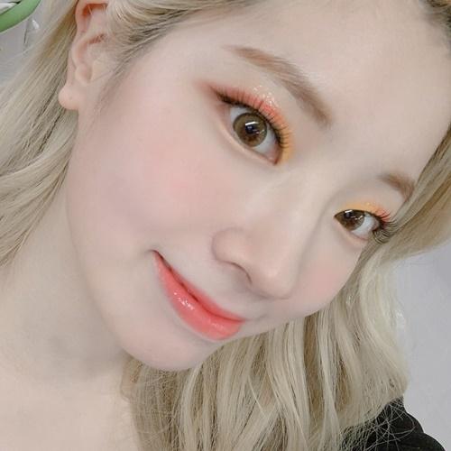 Da Hyun (Twice) trang điểm tông cam hồng ngọt ngào.