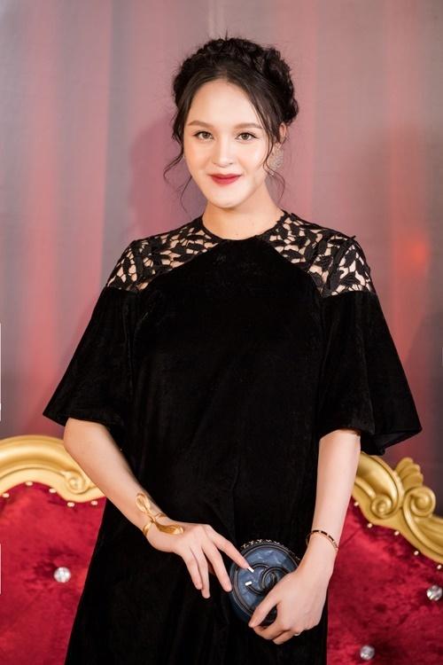 Á hậu Hoàng Anh bế bụng bầu 8 tháng đi xem thời trang. Cô mặc đầm suông, chất liệu nhung.
