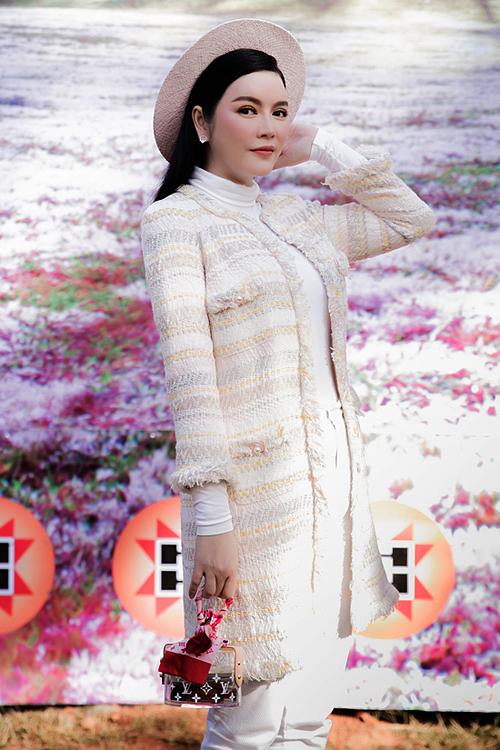 Lý Nhã Kỳ chọn phong cách thanh lịch khicông tác ở huyện Lạc Dương, Lâm Đồng. Cô mặc áo khoác của Chanel, áo cổ lọ Valentino và xách túi Louis Vuitton.