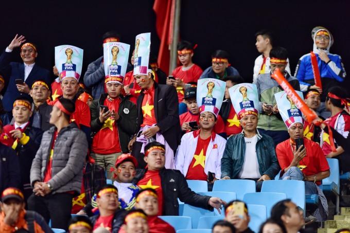 <p> Một nhóm CĐV in cúp vàng FIFA lên tấm biển đội đầu.</p>
