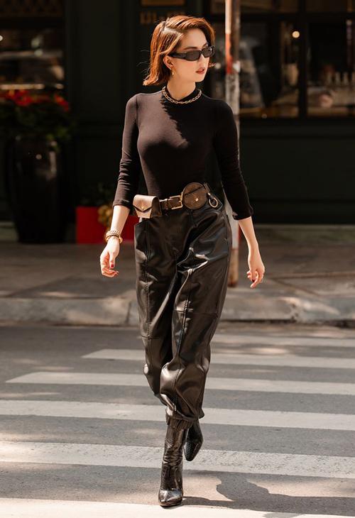 Chiếc áo cổ lọ đen cơ bản được Ngọc Trinh biến thành đồ chất lừ khi kết hợp cùng quần da và túi thắt lưng của Louis Vuitton.