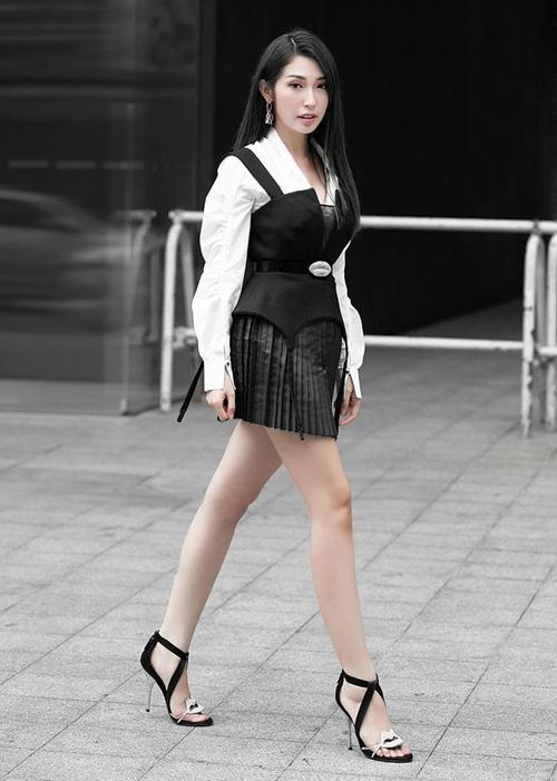Khổng Tú Quỳnh nữ tính khi diện sơ mi trắng kết hợp váy da xếp ly, đi kèm là sandals tông xuyệt tông.