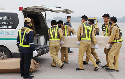 Quan tài của nạn nhân được chuyển lên xe cứu thương đưa về quê. Ảnh: TTX