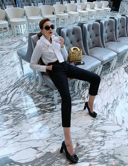Thanh Hằng diện sơ mi trắng kiểu tiểu thư nhưng vẫn toát lên nét quyền lực. Siêu mẫu xách túi Dior metallic làm điểm nhấn.