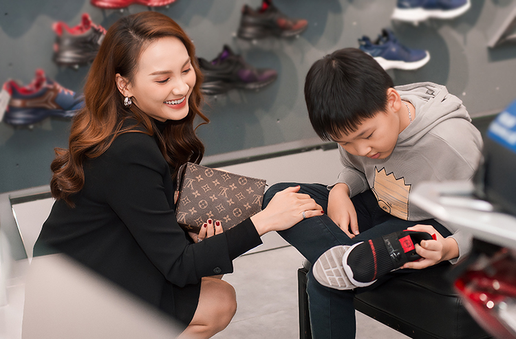 Nữ diễn viên cẩn thận chọn giày cho con trai.