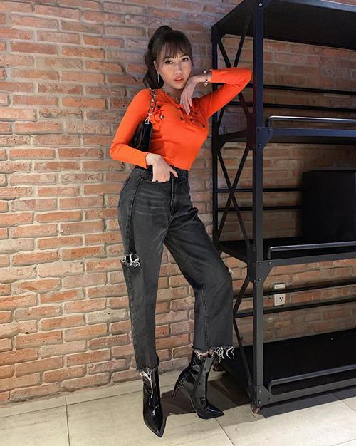 Diệu Nhi như biến thành người khác khi để tóc buộc cao, mặc áo cam màu nổi cool ngầu.