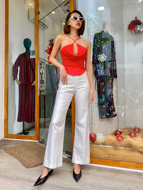 Minh Triệu nghiện mặc quần cạp cao ống loe tôn lên đôi chân dài. Chiếc áo hai dây màu đỏ giúp người đẹp khoe khéo vòng một.