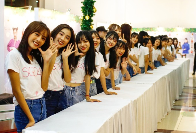 """<p> Tại sự kiện, nhóm cũng giới thiệu single thứ hai với sự xuất hiện của 16 thành viên tiếp theo sau single đầu tiên. Đó là những cái tên Anna, Trùng Dương, Kaycee, Janie, Hikari, Minxy. Họ sẽ góp mặt trong MV """"Koisuru Fortune Cookie"""" ra mắt trong những ngày tới.</p>"""