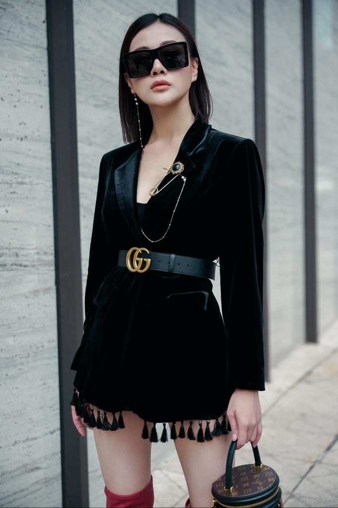 <p> Bộ trang phục tối màu trở nên cuốn hút hơn với khuyên tai phá cách, có thể cài lên áo.</p>