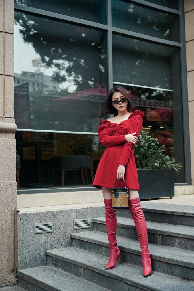<p> Nữ diễn viên<em> Quỳnh búp bê</em> biết cách làm mình nổi bật khi diện váy trễ vai màu đỏ phối với boots cao quá gối tông xuyệt tông.</p>